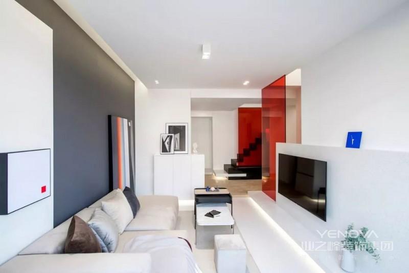 沙发背景由白色与深灰色块面组合,加上两幅装饰画,体块与电视机背景相呼应,每个物件都有自己存在的必要性。