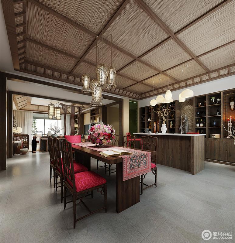 褐色实木以井字格饰以天花,铺陈出朴实质感,吧台、酒柜呼应天花色调,形成视觉上延续。餐桌椅的木色则选用棕色,加上娇红布艺、印花和花卉的装饰,空间显得灵动婉约。