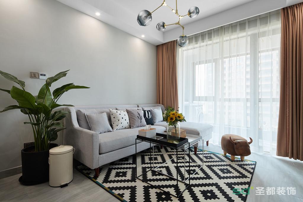 客厅的浅灰色沙发采用布艺代替,与黑白纹路的地毯相映,本来是中规中矩的黑白灰三色的搭配,在此基础之上搭配橘色元素的软饰,让空间一下子活泼起来。大胆的色彩搭配,总能在稳重中搭出新意,让