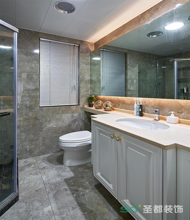 卫浴间采用浅灰色大理石纹的防滑砖,色彩搭配低调朴素。耐脏防滑的瓷砖非常实用。镜子周围一圈橘黄的灯光是点缀空间的亮点,弱化冷感增添空间的温馨感。
