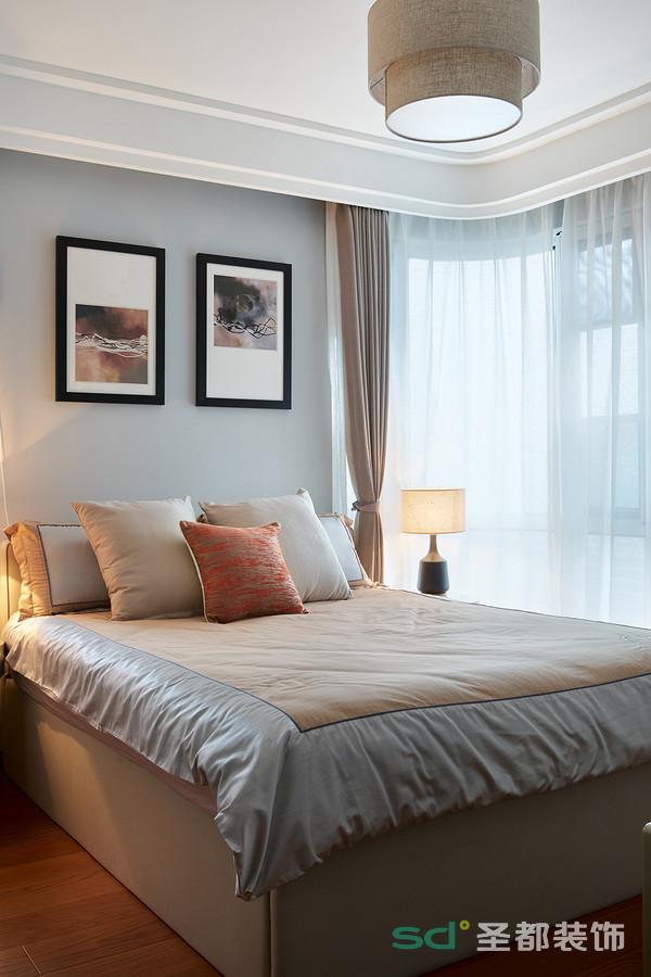次卧的色泽依旧以灰棕为基调,却因为床品、挂画、吊灯的选用,让整个空间明丽很多,打造出浓浓的温馨居家氛围。