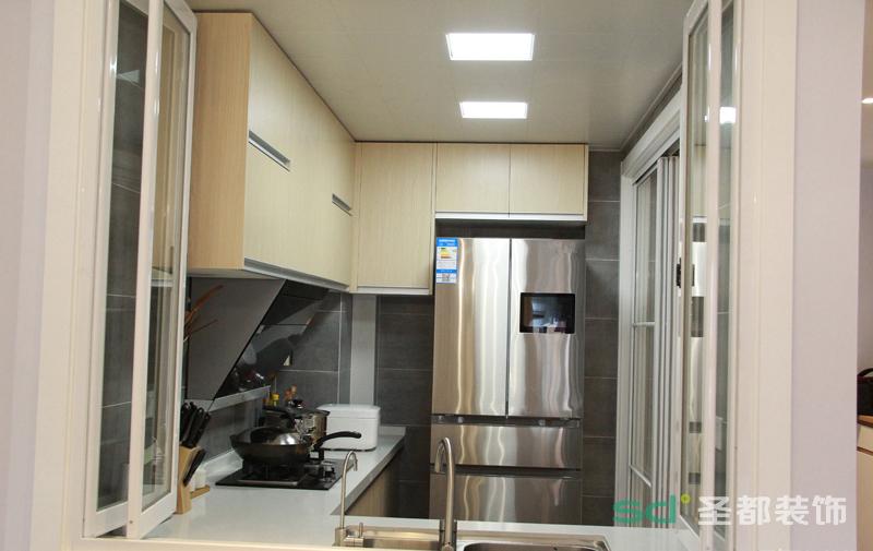 厨房的采光也较弱,但是设计师没有用传统做法将其封闭,做了一个半开放式厨房,当业主在做饭的时候即可以抵挡油烟,在整体的视觉感官上也增加了空间感。