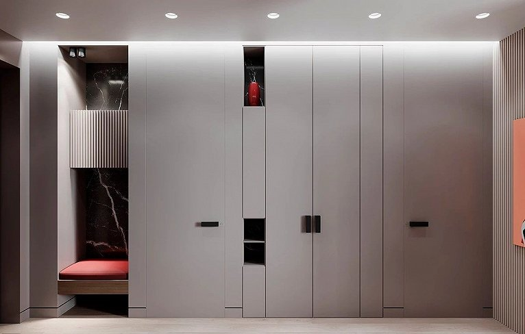 入口處巧妙的設置了一個內嵌式的座椅  為進出換鞋提供方便  一旁灰色的墻面包含兩個臥室門  以及一個雙開門柜子
