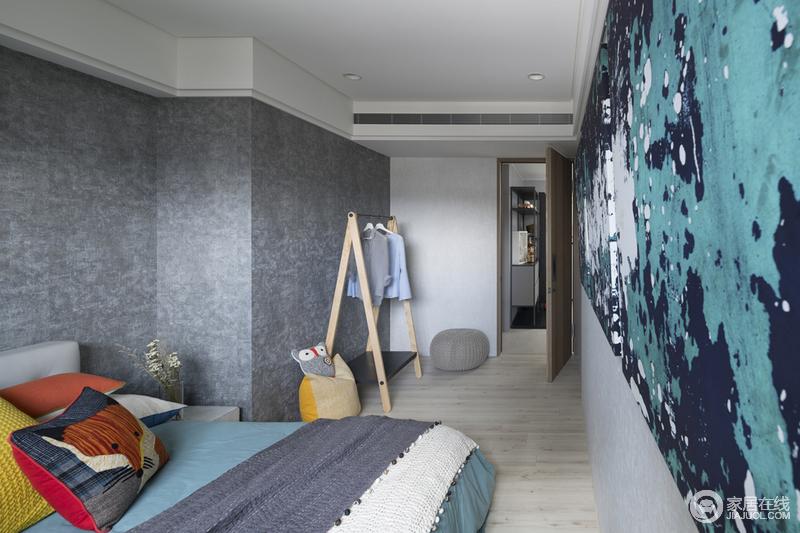 灰色壁纸十分素雅,人字形原木衣架轻快与布艺坐墩徜徉着自在;蓝、白等多色泼墨而成的巨幅抽象艺术画领携着空间的艺术基调,让卧室多了份文艺气息,并巧妙地利用床品将氛围升华,尤为时尚。