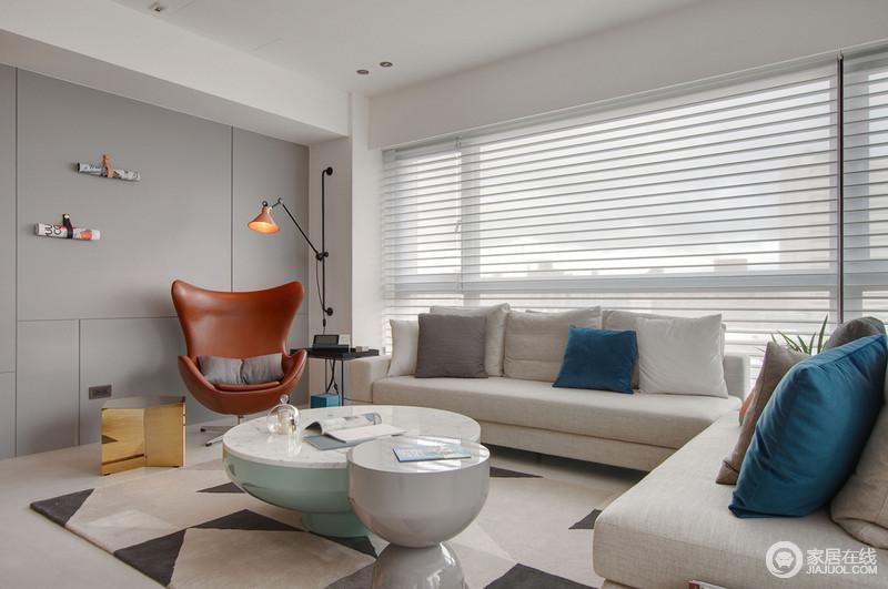 空间以灰、白为主色,以塑造安谧而素净的氛围;浅灰色沙发上白色、蓝色抑或灰色的靠垫点缀出现代时尚,棕红色转椅和金色边几个性而活力;墙上的微型饰品则妙趣横生,与圆形茶几组衬托出前卫。