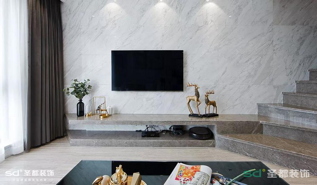 灰白色的墙面让整个空间更加静谧和有气质,电视柜则采用了大理石的台面,光线从落地窗透进来,整个空间十分明亮。