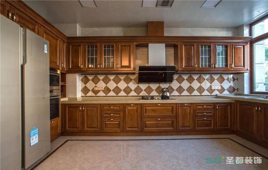 厨房是开放式的中西厨结合,烤箱、微波炉、冰箱都采用嵌入式设计,细节十分到位,尤其是吊柜部分,对称均匀但别出心裁,柜体全实木打造,门板采用了实木和艺术玻璃两种材料。这样一来,常用物品可通过透明门轻易寻找,其他东西放进木质门板的柜子,不影响厨房整体整洁美观,使厨房看上去更灵动。
