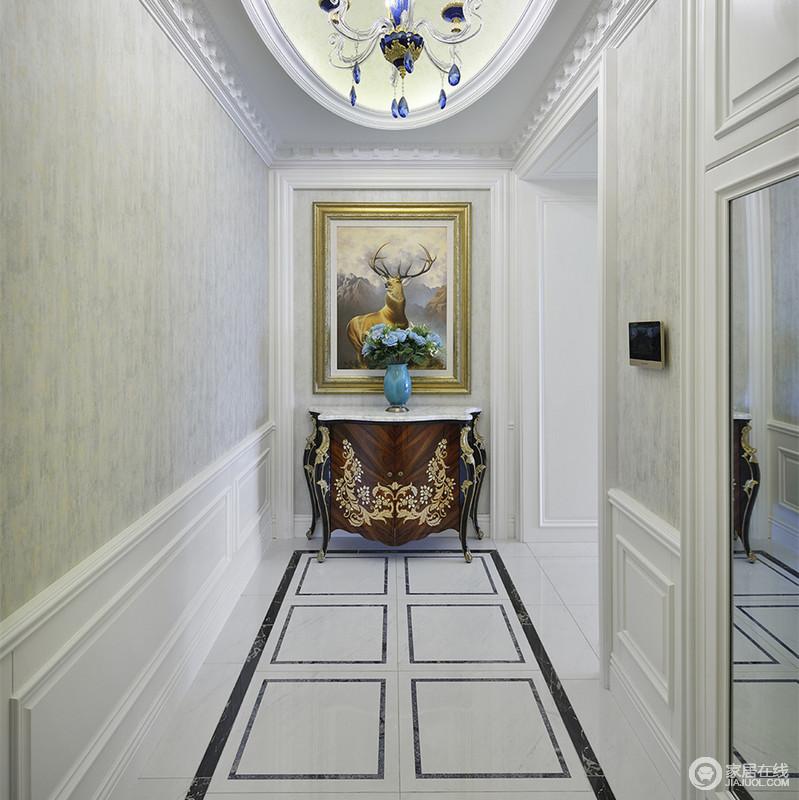 走廊以椭圆天花顶碰撞几何线条地板,制造上下的视觉感,加上镜面折射,减弱横向空间的狭窄。端景处描金雕花的古典边柜上,蓝色花瓶呼应客厅,并与画作图案点缀出自然情调。