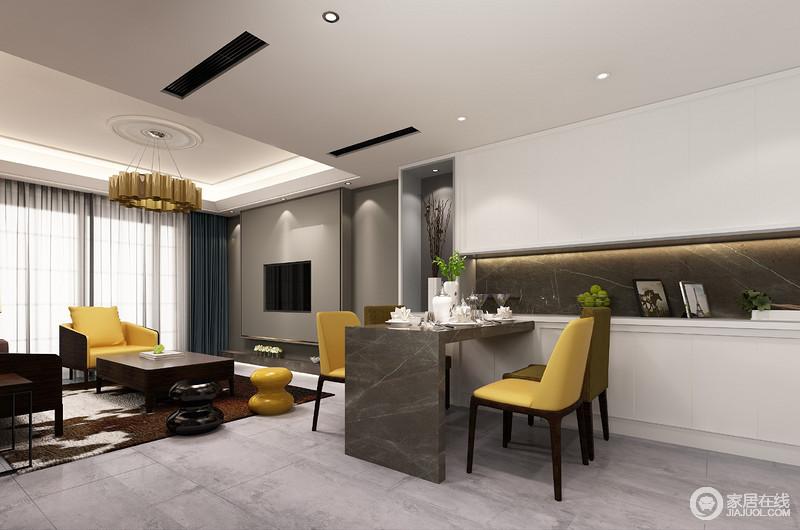 用心的设计丝毫不浪费空间,设计师将灰色大理石构成的微型吧台设置在白色收纳柜旁,与客厅紧密相连,构成一个功能性极强的设计;明黄色和咖色餐椅的现代感与客厅中黄铜圆盘吊灯张扬艺术之美。