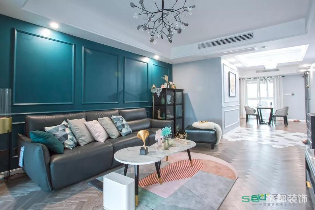 入户玄关的左手边是客厅,为了中和全屋的性冷淡风格,设计师将客厅的大背景墙规划成了孔雀蓝,用装饰线条勾勒出墙面的轮廓。