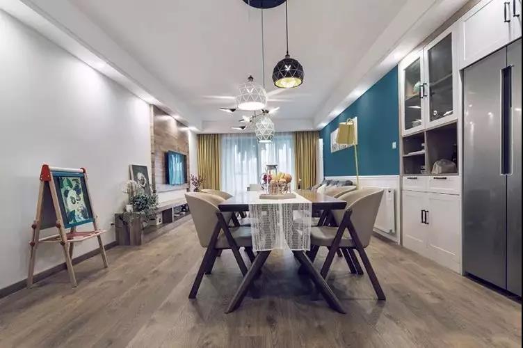 沿着入户动线即见餐厅,地面通铺进口地板,留白顶面设计垂吊三盏北欧风格吊灯。