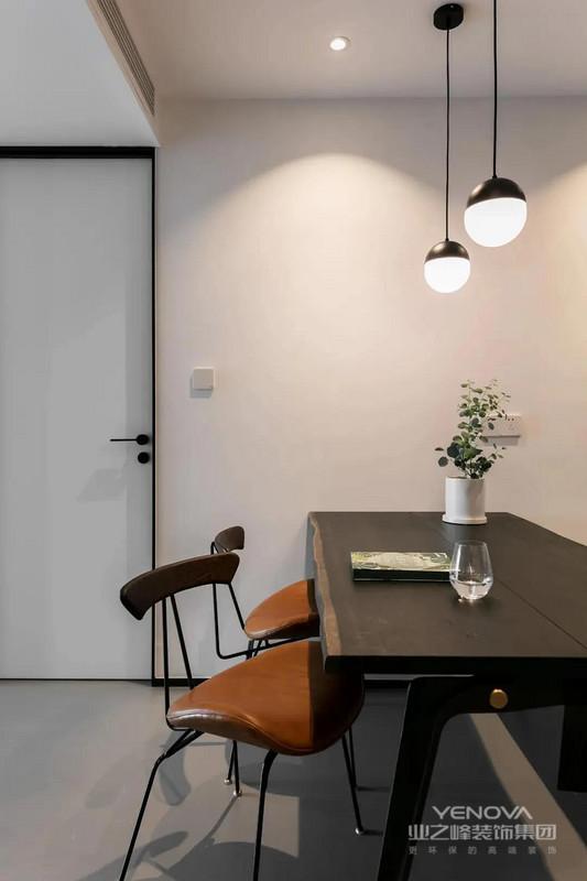 纹理细腻自然的深色餐桌,搭配两把细腿高脚餐椅和一把长椅就形成餐厅空间。在灯光的烘托下,氛围显得非常温馨。