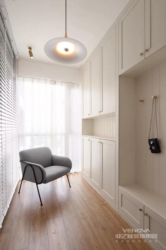入户门的侧方是一个玄关门厅空间,设计师在其中一侧做上到顶的鞋柜和换鞋凳,给窗户搭配百叶帘和纱帘,让玄关看起来更有一种朦胧美感
