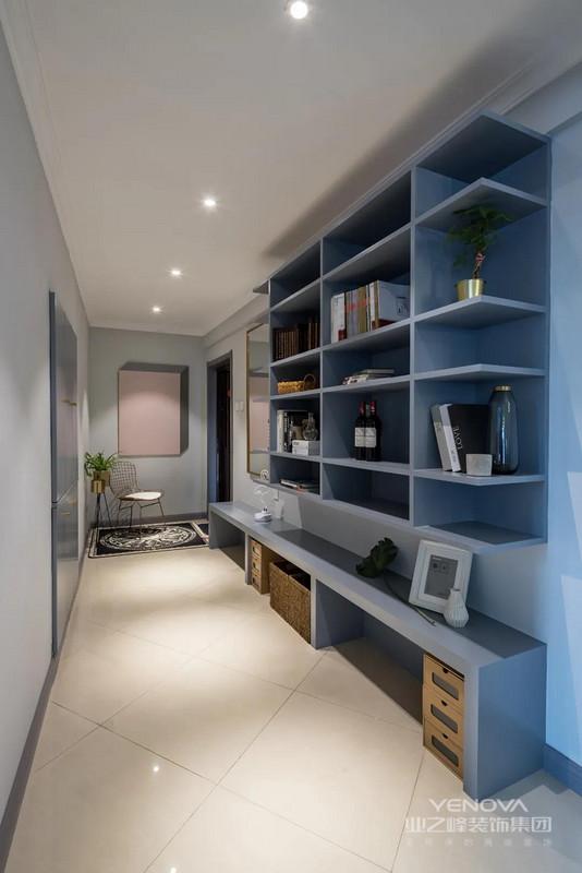 玄关是一个狭长的过道,大门右边的墙面挂一幅灰粉配创意装饰画,布置地毯与花盆,让回家空间充满精致的仪式感。而换鞋凳+吊柜收纳架的组合,还有入墙式的收纳柜设计,方便换鞋收纳之余,也提供了丰富的收纳与展示位置