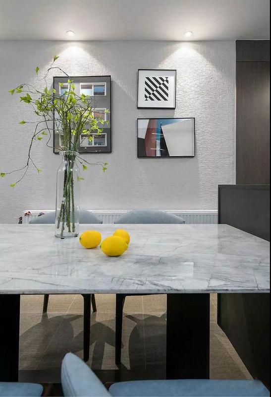 大理石餐桌自带清冷气质,背景墙选择组合挂画来丰富层次感,射灯洗墙晕染氛围,颇有情调。