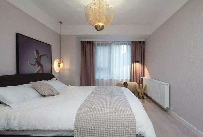 定制挂画简约又有艺术感,米色千鸟格抱枕及床尾搭毯自带优雅气质,和整个空间的雅致基调完美匹配。