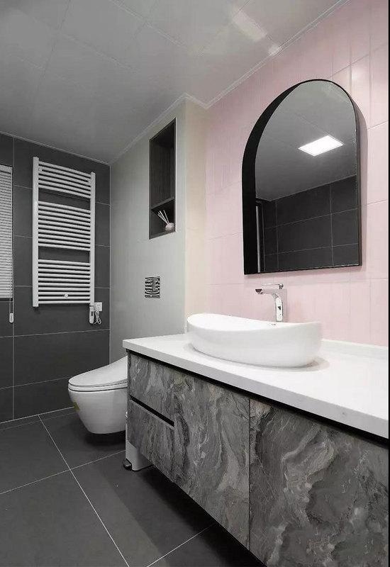 卫生间以简约的灰色为主调,浴室柜门别具一格,打破几何线条的规整感。墙面加入屋主喜爱的粉色以及柔和的浅黄色,整体新颖别致不失时尚感。