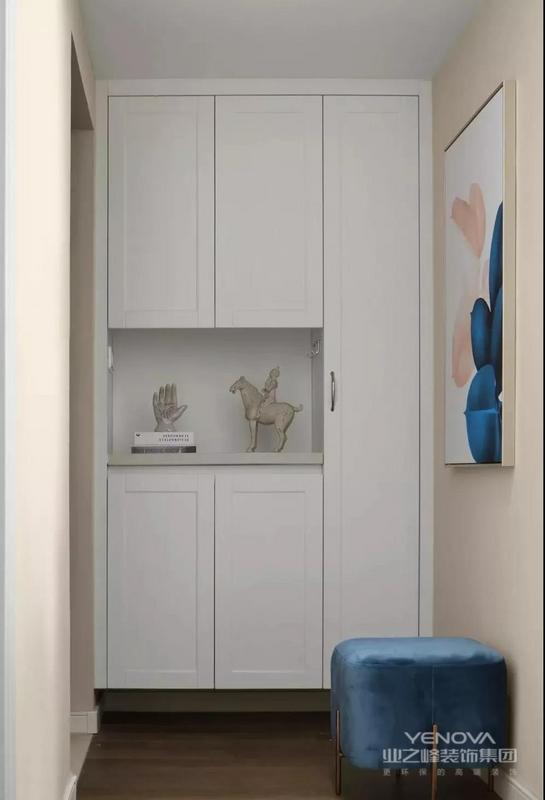 入户储物柜与蓝色丝绒换鞋凳形成视觉反差,增加一抹时髦亮色,装饰画与整体空间相呼应