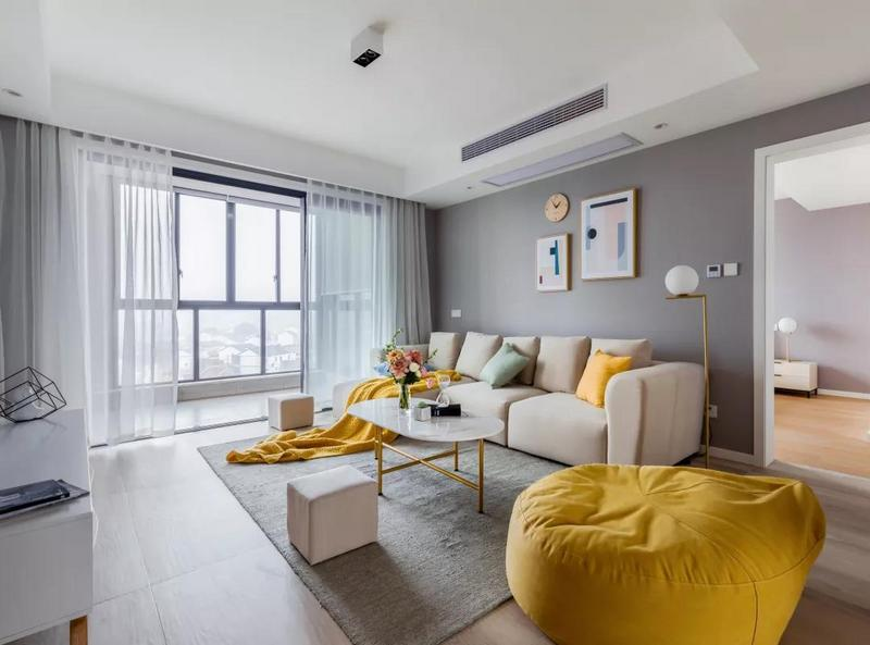 沙发墙的抽象几何挂画、还有时钟,让灰色调的背景墙显得更加艺术气质;米白色布艺沙发,搭配上鲜艳的黄色懒人椅与抱枕软装,在这个简约的空间里显得格外的抢眼,点亮了空间的活泼感。