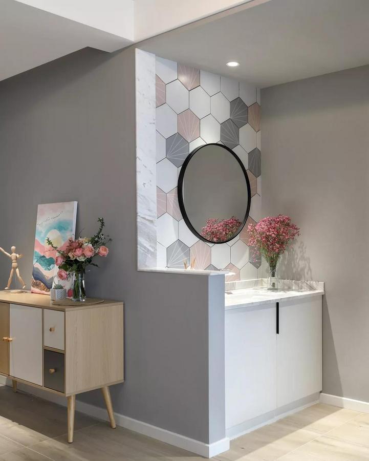 公卫的洗手盆设置在过道区域,以矮墙为隔断,墙面在灰白粉色的六边砖搭配下,挂上一面圆形的黑框镜子,布置出一种北欧范的舒适体验。