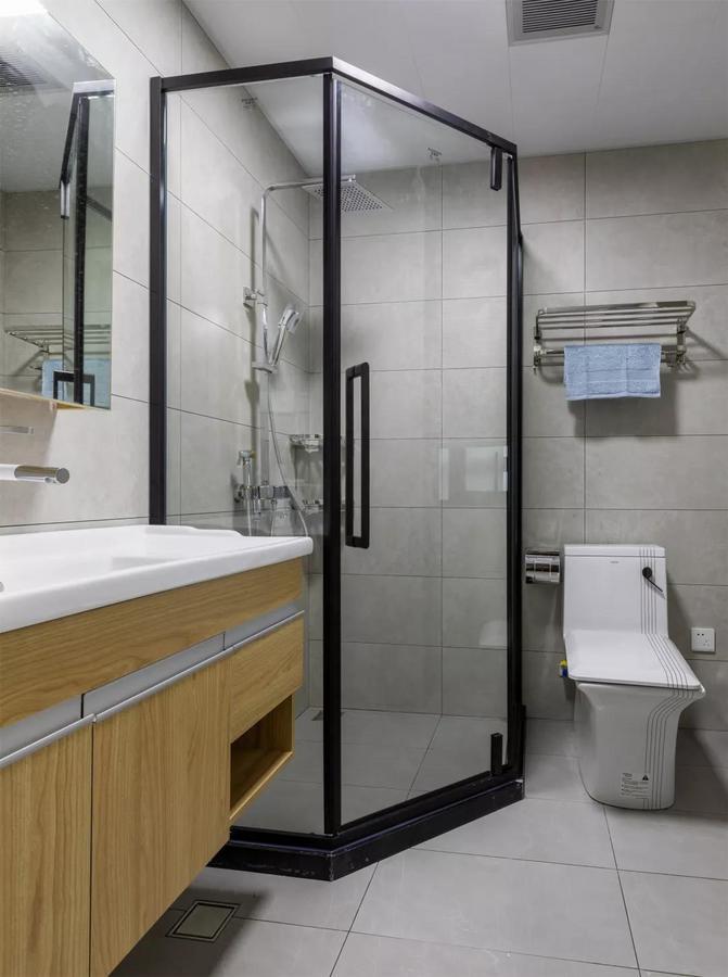 卫生间在哑灰色的空间基础,搭配黑色淋浴房,再布置上木色洗手盆,呈现出一种冷暖交融的对比感。