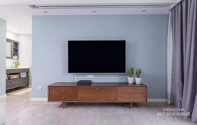 电视背景墙上没有做任何装饰,简单的刷上蓝色乳胶漆就好。客厅的侧边就是卫生间的干区,洗手台刚好被嵌入进了凹槽内