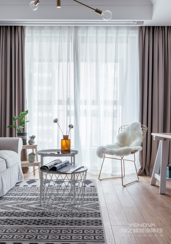 客厅有面大大的落地玻璃窗,大量光线能照进室内,整个客厅采光特别棒。白色镂空小圆桌加白色小茶几,搭配金色铁艺休闲椅,简约不失精致感。