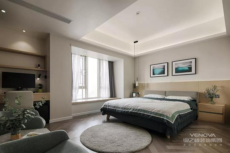 主卧室的空间非常宽敞,鱼骨铺贴的木地板和木质床头背板让整个卧室充满了设计感,在床尾的空间处还摆放了沙发和书桌。