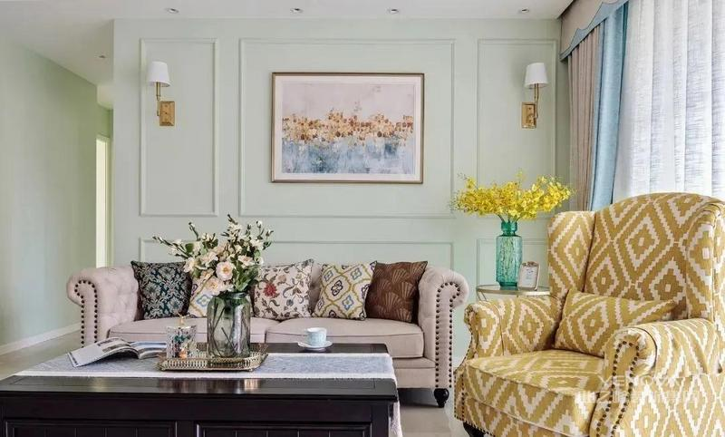 薄荷绿背景墙勾勒石膏线条 搭配经典的铆钉沙发 浓浓的美式格调 休闲舒适