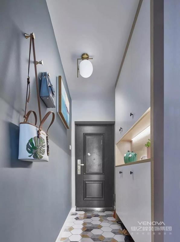 入户的玄关走廊处做了到顶的嵌入式鞋柜,鞋柜底部和中间留空,还加入了藏光的设计,方便日常使用。地面铺贴文艺范十足的六边砖,搭配灰色系墙面很好看