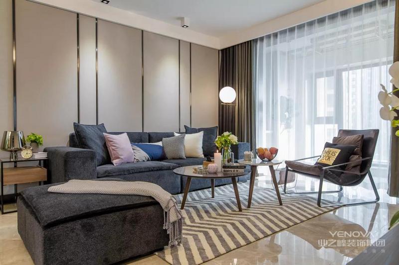 客厅的沙发背景墙上做了灰色硬包加金属线条的设计,做旧款的蓝色布艺沙发集合波浪纹的地毯,整个客厅的设计简洁而又时尚