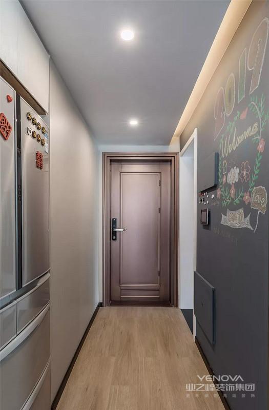 入户玄关走廊的墙面做了黑板墙的设计,搭配一些自己喜欢的图案非常漂亮。另一侧的墙体做了部分的嵌入式设计,把冰箱给放在了这里