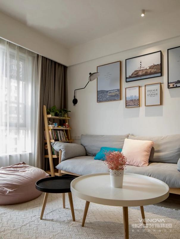 采用大张地毯搭配灰色 沙发规划出客厅场域 白色文化砖铺贴成沙发背景 点缀艺术挂画