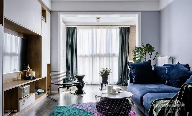 客厅,一整面的落地窗让光线直射进来,室内非常明亮。海蓝与原木的色系,仿佛沐浴在夏日海岸明媚的气息里。双色拼接的毛绒地毯让人眼前一亮,奔放热烈的气息扑面而来。