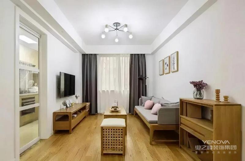 实木框架搭配浅灰色坐垫的沙发,上面放两颗烟粉色的心形抱枕,空间显得活泼灵动。大白墙在三幅小挂画的点缀下,简约时尚。