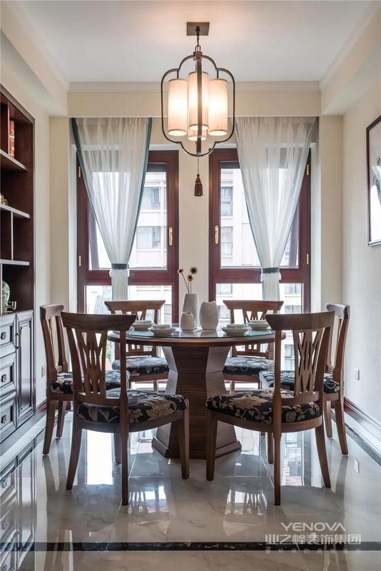 餐厅的一侧做上嵌入式的餐边柜,圆形餐桌椅被波导线给包围起来,顶部的中式风吊灯给餐厅带来了更禅意优雅的感觉。