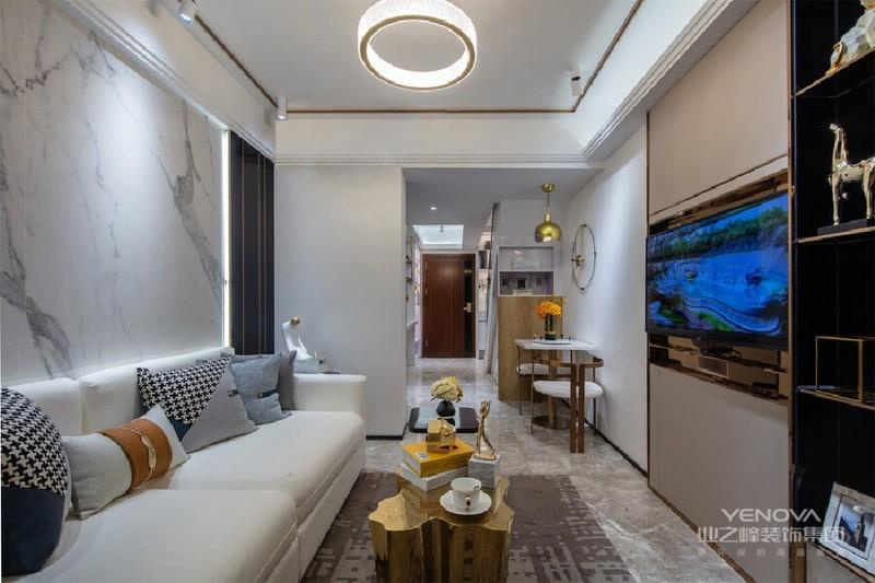 客厅整体空间现代简约,雪花白岩板、米黄色硬包和灰色地砖相搭配,空间色调于明暗变化间无形为空间带来放大的效果。由上至下,现代感气息之余更具浓郁家居生活氛围。