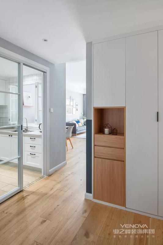 入户是一个玄关门厅的空间,设计师还做了嵌入式的鞋柜,进一步的提升了玄关门厅的面积。厨房位于玄关的侧方,用玻璃推拉门作为隔断