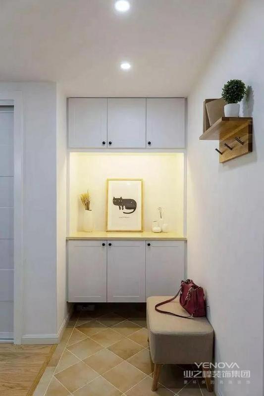 进门右侧墙面上安装一个实木衣帽钩搁板,可以挂出门常用的帽子、围巾、外套等。玄关柜镂空设计,还用灯带装饰,提升整体颜值。