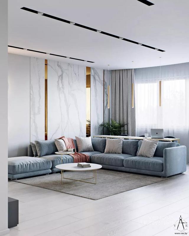 开放式客厅,整个空间简洁,灰白的大理石,蓝色布艺沙发,木质的地板,大大的窗搭配灰色的窗帘,光线充足,餐厨在客厅的一边,没有隔断,黄铜的点缀非常抢眼,时尚轻奢,色彩协调。
