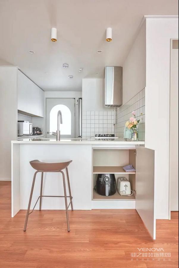 厨房采用L型布局,半开放式设计,无把手柜子搭配大单槽,看起来干净利落。吧台的设计实现了双面收纳,烹饪小家电直接放在这里,设计的灵活性让这个空间变得与众不同。