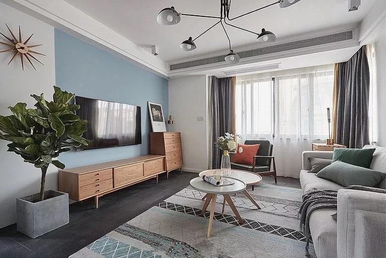 客厅处用天蓝色的背景墙搭配白墙,有着蓝天白云的感觉,让人感觉宽敞而又明亮,再加上原木风的电视柜、绿植带来的自然感,更加惬意。
