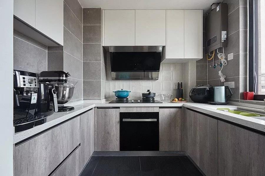 U型的厨房布局,深灰的地砖,浅灰的墙面,配合上白下灰的橱柜,不会压抑的同时显得高档整洁。
