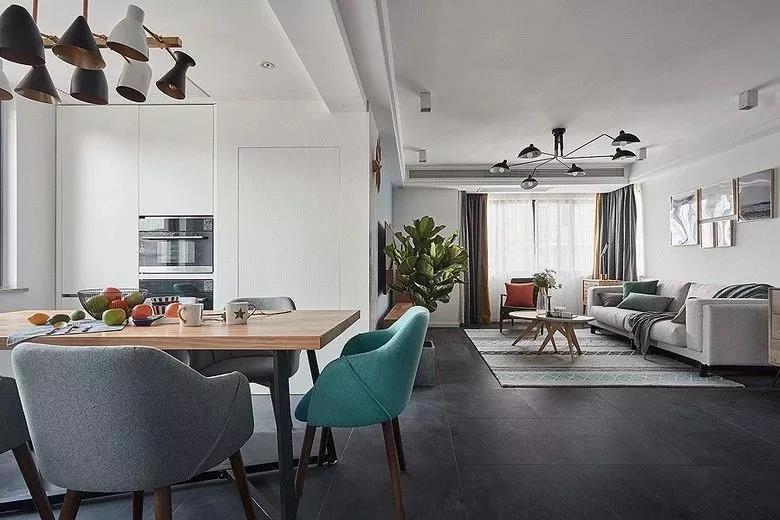 客厅和餐厅之间没有做隔断,地面铺设了深灰色的哑光砖,让整体色调为白色的空间多出了高级感和格调感。