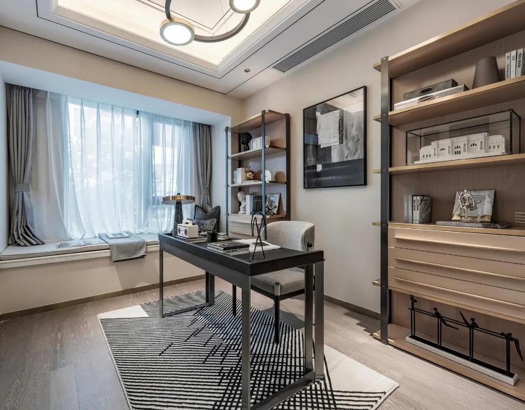 书房空间中摆上一张办公桌,书桌后方挂一幅黑白调的装饰画,两侧布置上成品书架,呈现出一种华丽优雅的舒适气质。