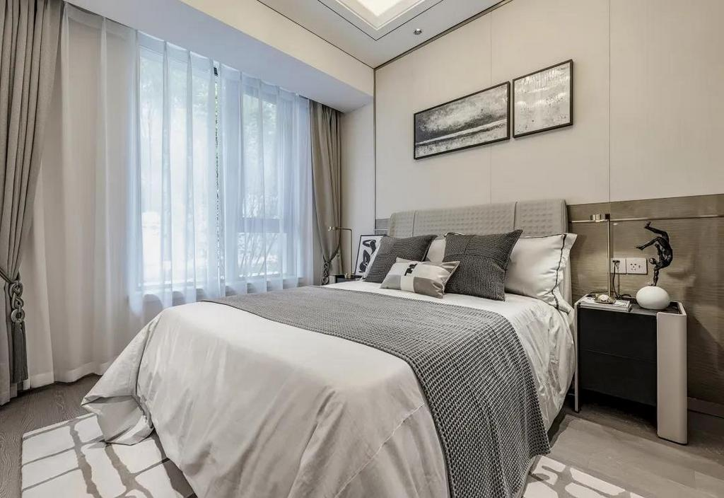 次卧床头墙以硬包处理,墙脚区域稍微深色,挂上两幅黑白调的装饰画,再布置以皮质的床铺,让睡眠空间充满舒适从容的轻松氛围。