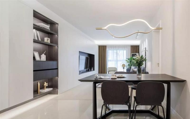 深木色的餐桌靠墙而立,配合一盏造型轻盈的吊灯,充满写意悠闲的情调。