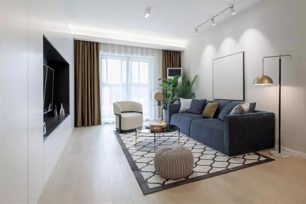 客厅,电视内置于收纳型的电视墙上,沙发墙挂了一幅简约纹理的装饰画,配合射灯以及原木色的地板,奠定了简洁利落的基调。