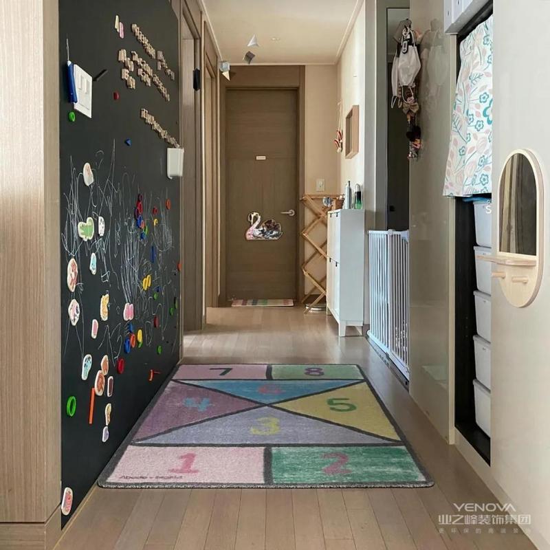 一开门就看到磁力吸黑板墙,这是业主夫妻为孩子创造的拼图空间。下面还铺着色彩丰富的地毯,孩子们可以自由自在玩耍