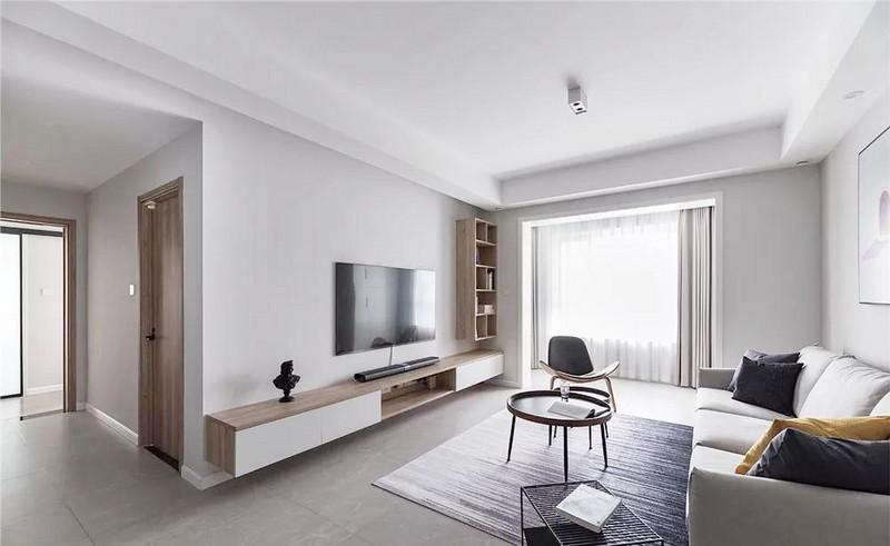 空间采用无主灯设计,客厅中央上方有一处明装射灯,可自由调节照射角度。